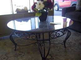 round glass top table with metal base round glass top table and black wrought iron base on areas rug of