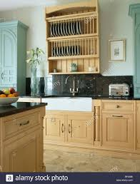 pale wood plate rack and granite splash back above belfast sink in