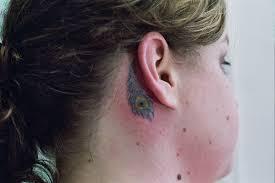 tiny peacock feather design on ear tattoomagz