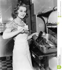 young woman basting a goose in the kitchen stock photo image