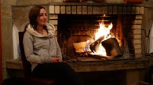 auburn beauty young woman warming up at fire place in winter lady