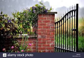 open wrought iron decorative garden gate hanging off brick pillar