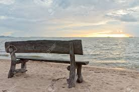 wooden bench on the beach with sunset stock photo picture and