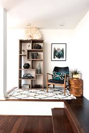 bright white reading nook with bookshelf chair and printed rug