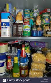 Kitchen Cupboard Shelving Tins And Packets Of Food On Shelves In A Kitchen Cupboard Stock