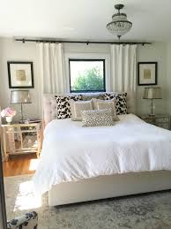 neutral bedroom window behind bed bedroom window treatments