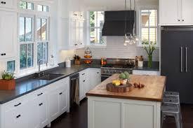 all white kitchen with black appliances