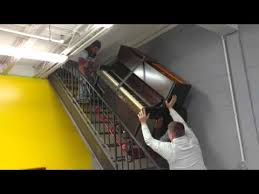 three guys moving a piano up a flight of stairs youtube