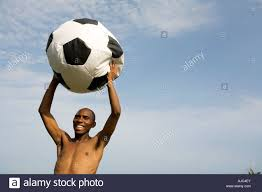 man holding a soccer ball bean bag in the air stock photo royalty