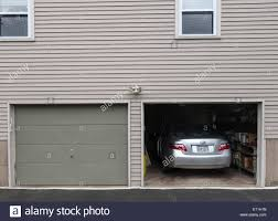open garage door with car parked inside american style wooden