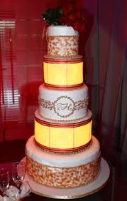 5 layer white wedding cake with gold fondant draping and fresh