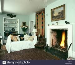 country livingroom with fire lit in fireplace and sofa with white