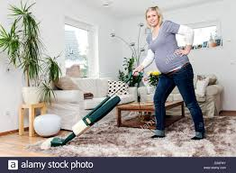 vacuum the carpet a pregnant woman in living room with a vacuum cleaner a