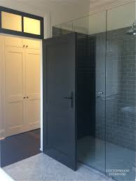 black doors dark gray subway tiles herringbone marble floor