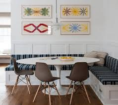 dining room brown eames chairs with white round table and wall