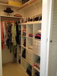 white wooden for small closet with cube shelves and clothes