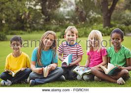 classmates books classmates sitting in grass and reading books stock photo royalty