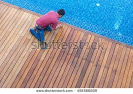worker painting exterior wooden pool deck stock photo 456566809