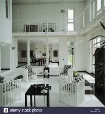 black and white cushions on white chairs in double height modern