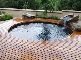 attractive wooden deck for small pool designs with stone waterfall