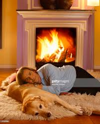 man reading magazine in front of fireplace stock photo getty images