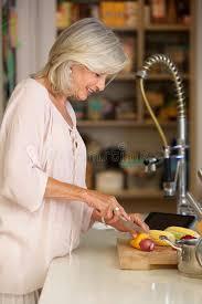 femme plus cuisine légumes de coupe de femme plus âgée dans la cuisine moderne photo