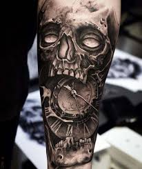 black and gray clock and skull tattoos on bicep
