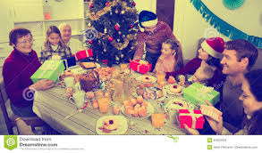 large family exchanging gifts during christmas dinner stock photo