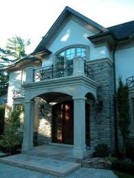 CURB APPEAL – three stories of stone and stucco wonderful shutters arches and balconies pavers instead of a concrete sidewalk clipped box shape…