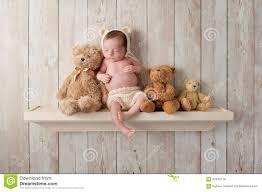 newborn baby boy on a shelf with teddy bears stock photo image