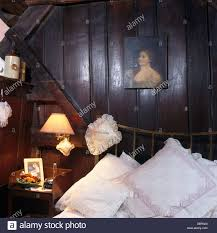 small painting on dark wood paneling above bed piled with white