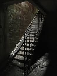 crumbling staircase in the basement of a derelict insane asylum in
