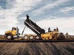caterpillar ct660 dump truck and a cat road paver heavyhauling
