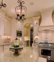 dark grey island with white countertop and antique white cabinets