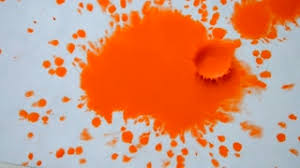 orange paint red orange ink paint droplets spreads on the paper wet white