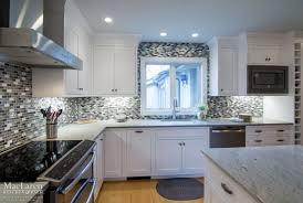 granite countertop white kitchen cabinets with glass tile