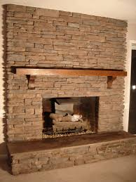 beige stone fireplace mantel with brown wooden shelf and beige