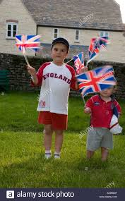 boy and wearing england football shirts and waving england