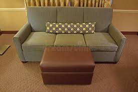 Narrow Ottoman Grey Fabric Sofa With Brown Leather Ottoman And Narrow Pillow