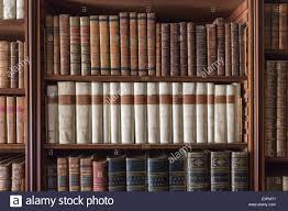 antique books lined up and neatly displayed on bookshelves in