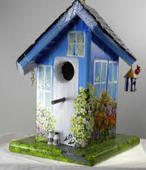 twisted birdhouse painted blue with it s own bird house and