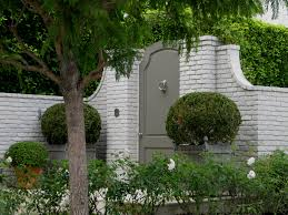 elegant painted garden gate in painted brick wall boxwood in wood
