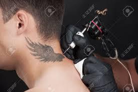 professional tattooist drawing beautiful wings on neck