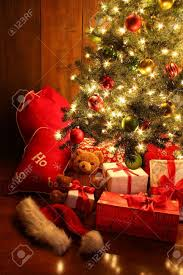 closeup of brightly lit christmas tree with gifts stock photo
