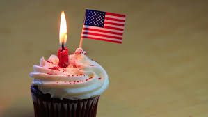 one patriotic birthday cupcake with a burning candle and a tiny