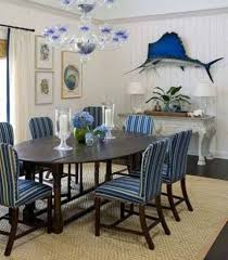 beach dining room design with wall decor and striped chairs
