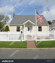 american flag pole suburban bungalow style home white picket fence