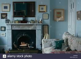 mahogany mirror above marble fireplace in pale blue country living