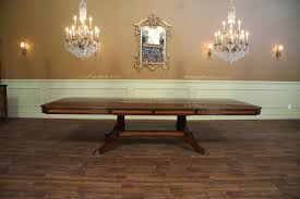 large mahogany dining table with self storing leaves table opened with two leaves shown at 132 inches and seats 12 to 14 people