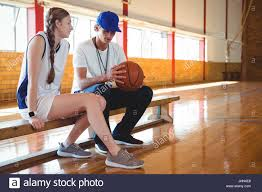 basketball player on bench coach talking with female basketball player while sitting on bench